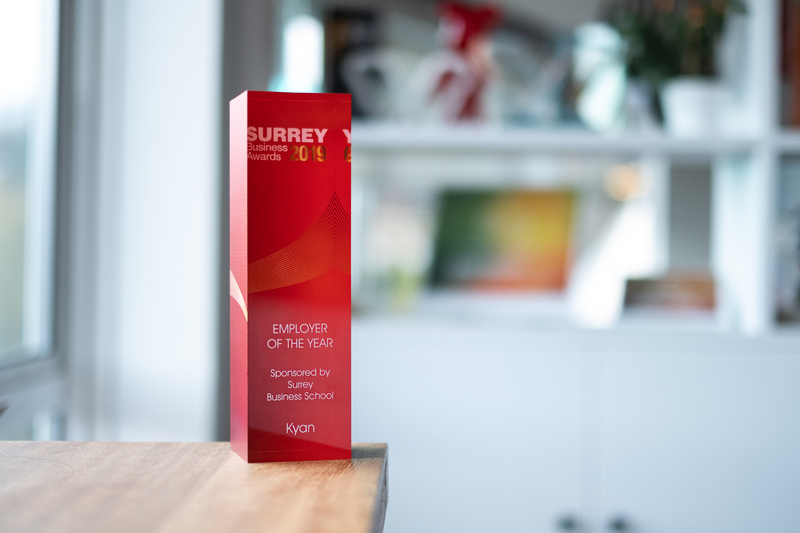 A red resin trophy displayed in front of other awards at the Kyan office.