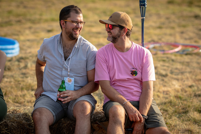 Harry and Gav sitting on a hay bale drinking beer during golden hour.